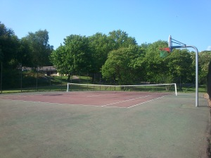 The football ground and the tennis court are located next to each other and are just across the street from the building